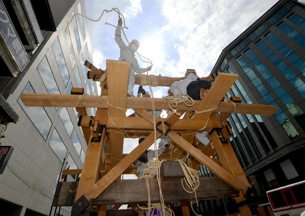 縄を使って「函谷鉾」を組み立てる職人ら=10日午前、京都市下京区(永田直也撮影)