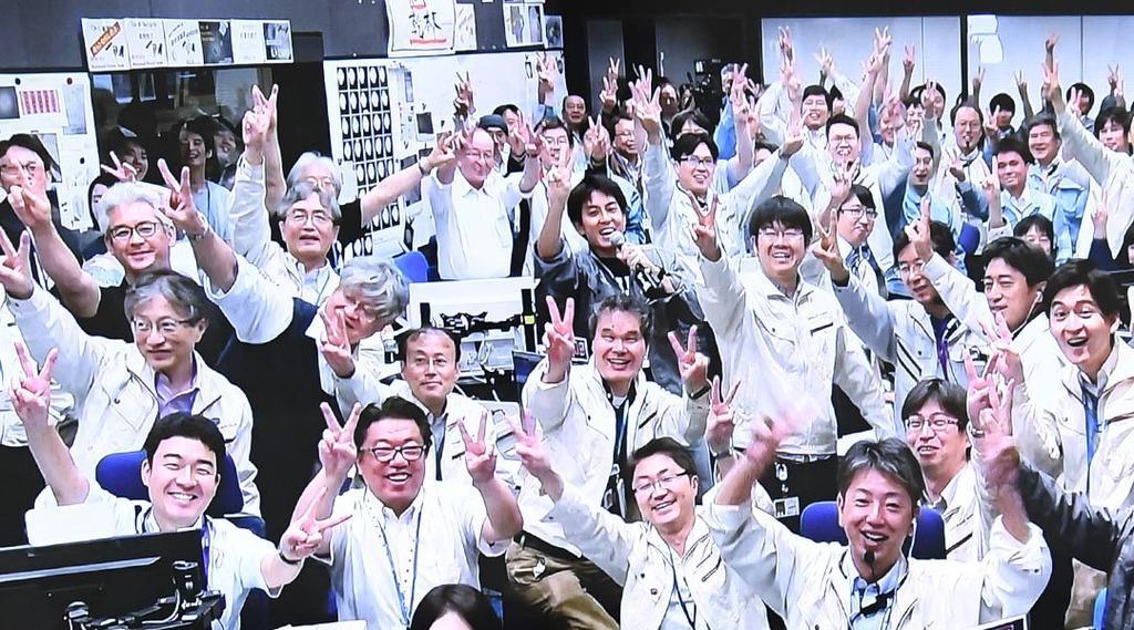 小惑星探査機「はやぶさ2」の第2回目着地の成功が確認され、ピースサインで笑顔を見せるJAXA職員ら。モニター映像が管制室の様子を映し出した=11日午前、相模原市のJAXA相模原キャンパス(寺河内美奈撮影)