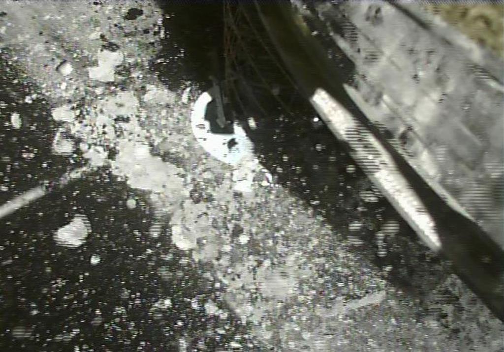 探査機「はやぶさ2」が小惑星「リュウグウ」着地の4秒後に撮影した画像。多数の岩石が飛び散っているのが分かる。右上は機体の一部=令和元年7月11日(JAXA提供)