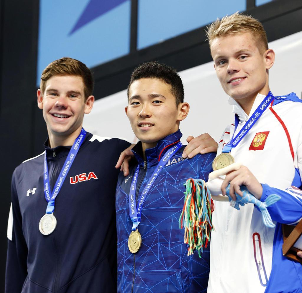 競泳男子400メートル個人メドレーで優勝し表彰台で笑顔を見せる井狩裕貴(中央)=ナポリ(共同)