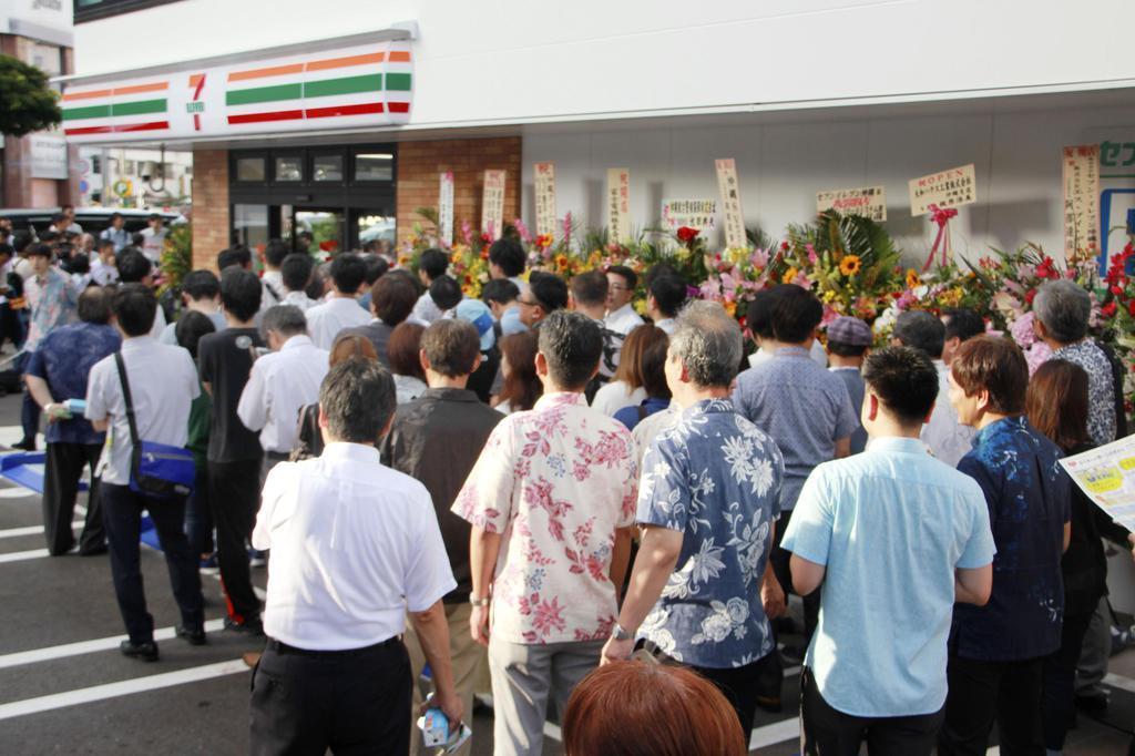 セブン-イレブンが開業し、店の外に並ぶ客=11日午前、那覇市
