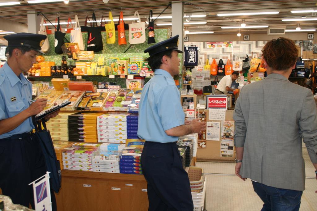 道後商店街で店舗を1軒ずつ訪れ、火災予防を呼びかける松山東消防署員=松山市