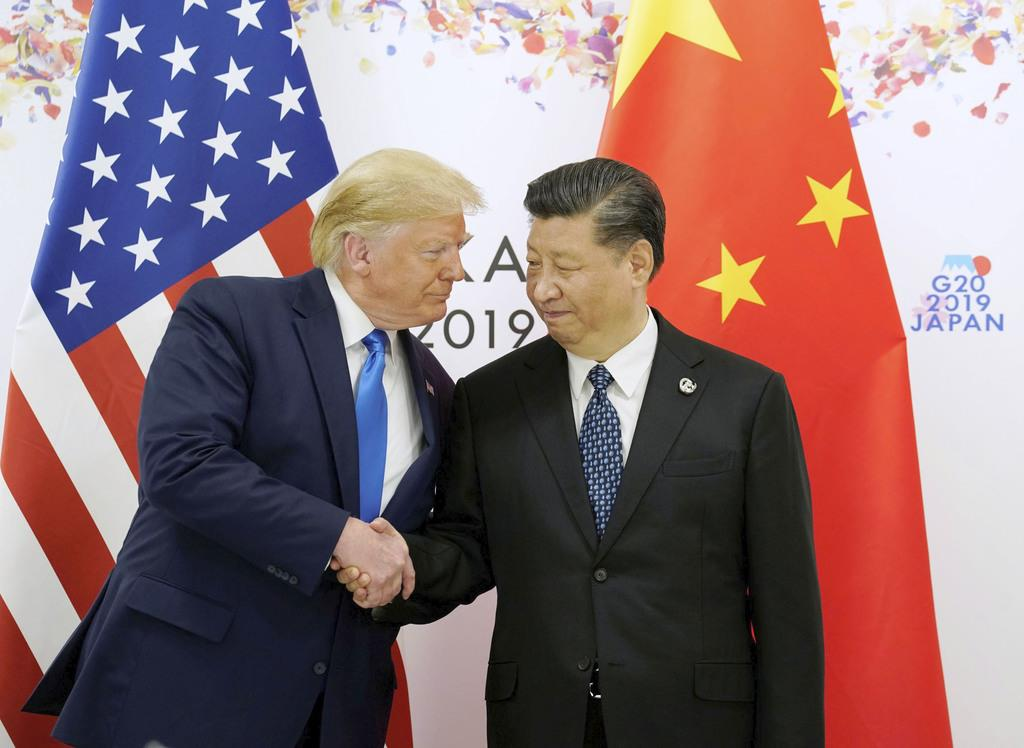 約7カ月ぶりの会談を前に握手するトランプ米大統領(左)と中国の習近平国家主席。会談では貿易問題の解決に向けた協議の継続で一致した=6月29日午前、大阪市(ロイター)