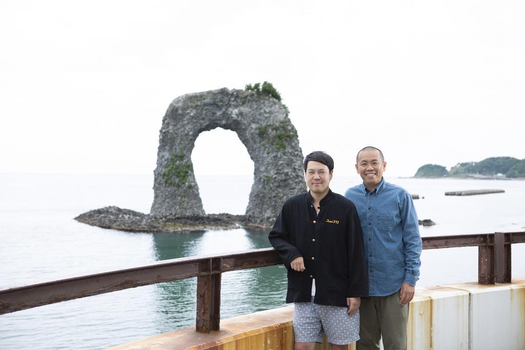 奥尻島のシンボル「鍋釣岩」をバックに記念撮影するタカアンドトシ(右)(C)UHB/YOSHIMOTO KOGYO