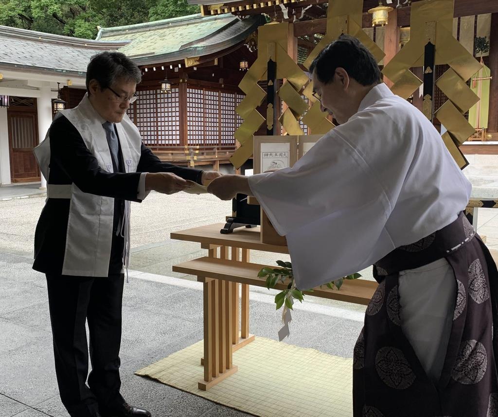 西宮神社の吉井良英権宮司(右)から頒布委託状を受け取る藤崎三郎助社長=西宮市