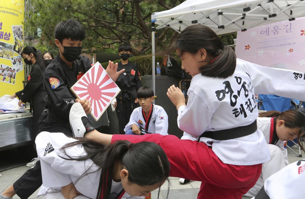慰安婦問題で日本政府に補償を求める抗議集会。参加者の韓国の小学生が日章旗に蹴りを入れ、対日感情の悪化を煽った=10日、ソウルの日本大使館前(AP)