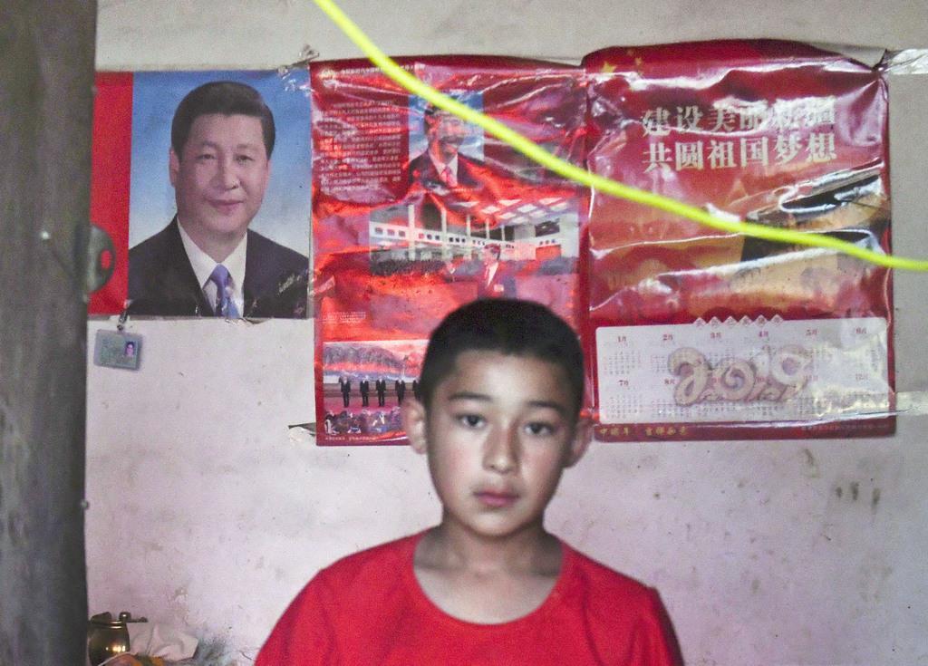 店舗に張られた中国の習近平国家主席のポスター=3日、中国新疆ウイグル自治区南部のホータン地区(共同)