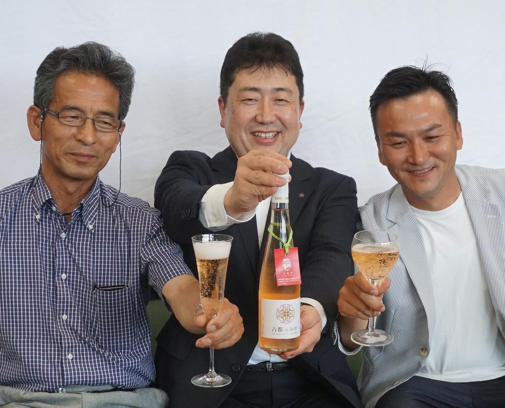 古都華を使ったスパークリングワインの完成を喜ぶ今西栄策さん(中央)ら=奈良市