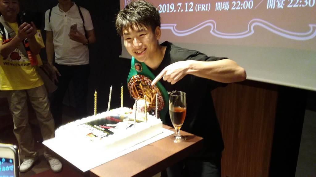 関大後援会が用意した祝勝ケーキを前に笑顔をみせる拳四朗=大阪市内