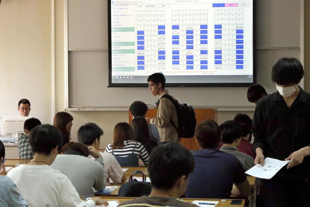 全席指定席の授業を行う阪南大。スクリーンに映し出された席順に座る学生。スマホで教授から口頭で伝えられるパスワードを入力し出席となる=29日、大阪府松原市(前川純一郎撮影)