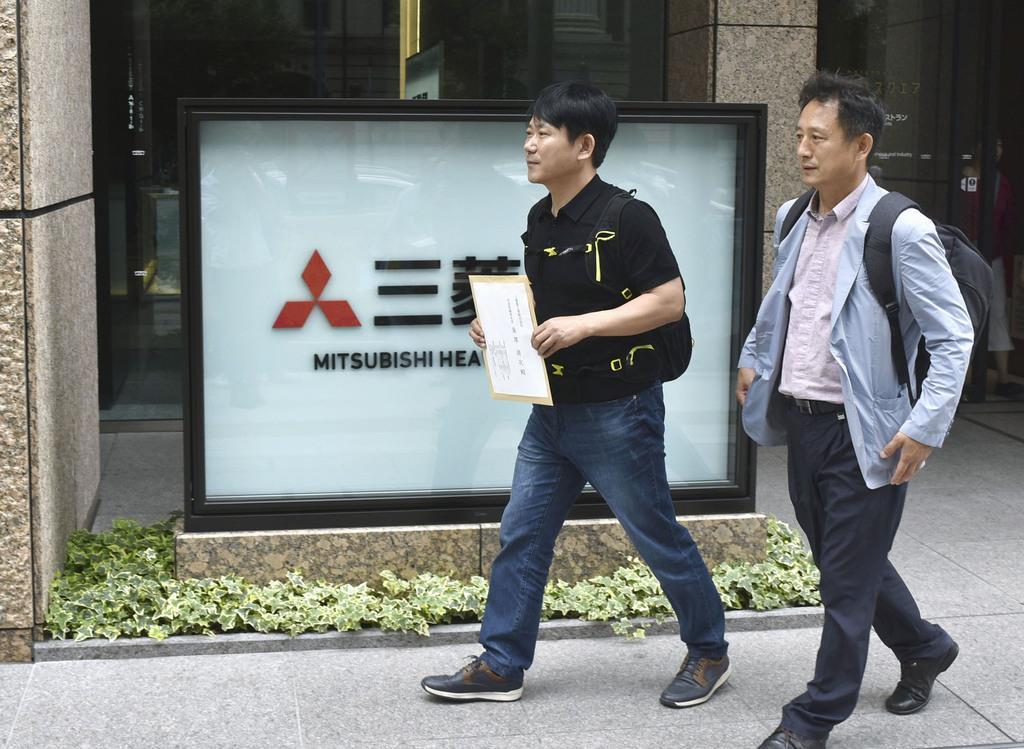協議要請のため三菱重工業本社を訪れた韓国の弁護士(左)ら=6月21日午前、東京都千代田区