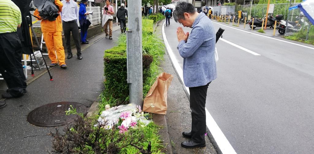 現場に花を手向け、手を合わせる男性=7月19日午前、京都市伏見区(西山瑞穂撮影)
