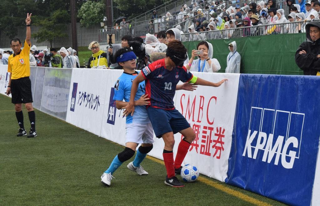 サイドフェンス際でボールを奪い合うfree bird mejirodaiの鳥居健人選手(左)と埼玉T.Wingsの加藤健人選手