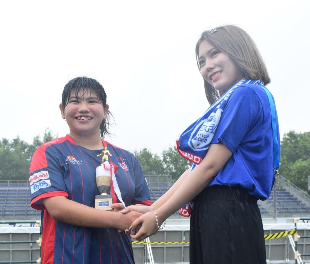 MVPのトロフィーを胸に握手する菊島宙選手(左)と、今大会の「大会応援マネージャー」を務めたタレントの川後陽菜さん