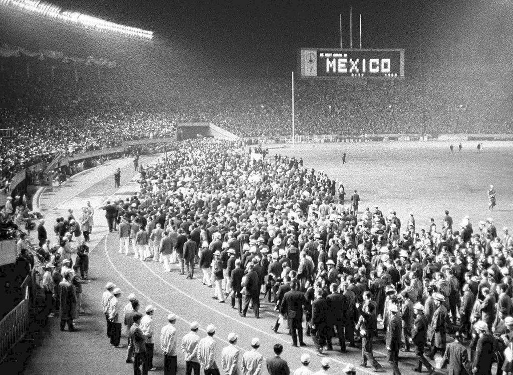 東京五輪の閉会式では各国選手が自由気ままに行進した。「電光掲示板にメキシコで会いましょう」の文字が見える=昭和39年10月24日、国立競技場
