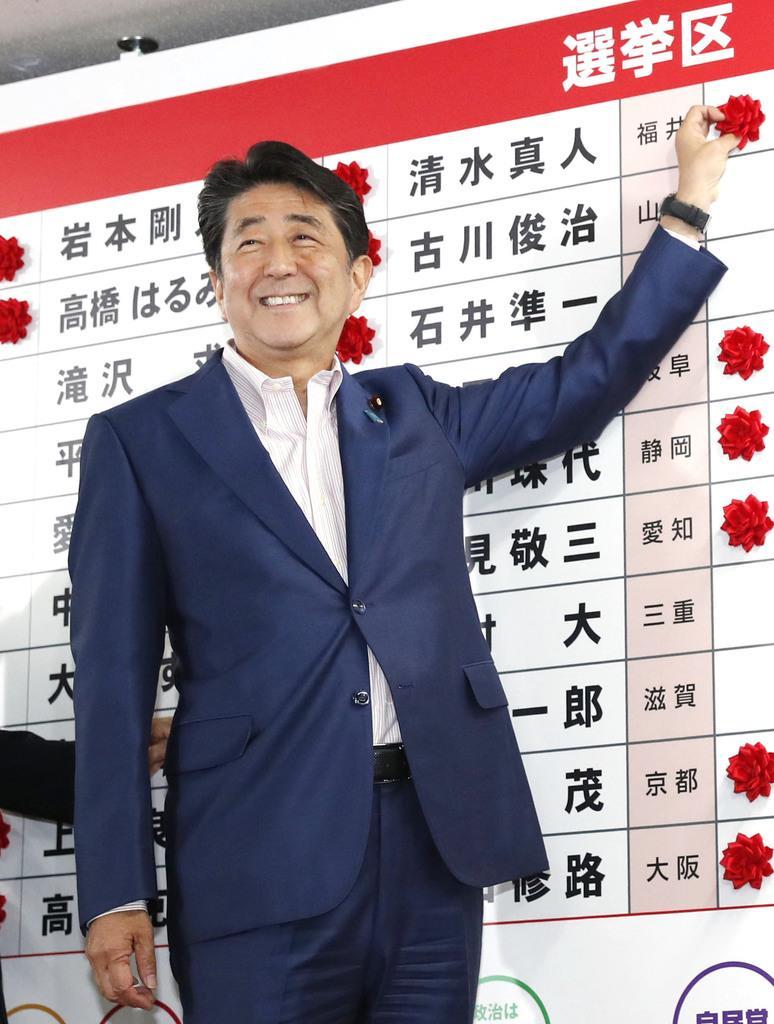 自民党本部の開票センターで、当確者の名前にバラを付ける安倍首相=21日午後9時55分、東京・永田町