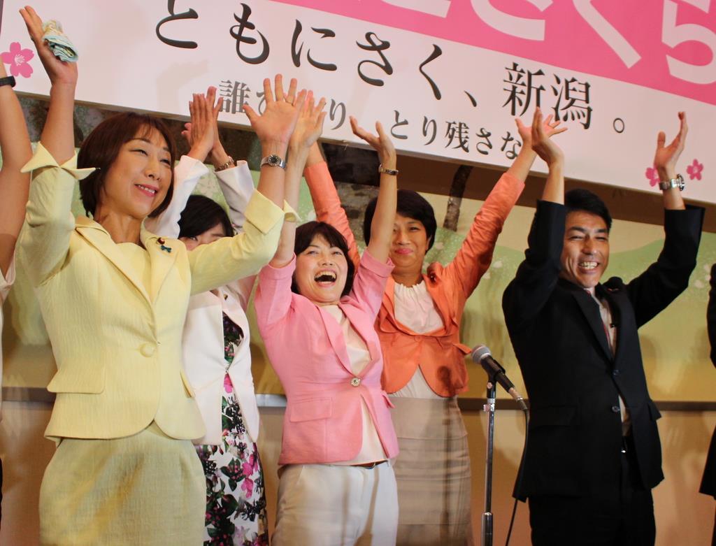 当選を確実にし、万歳する打越さく良氏(中央)=21日午後10時ごろ、新潟市中央区(池田証志撮影)