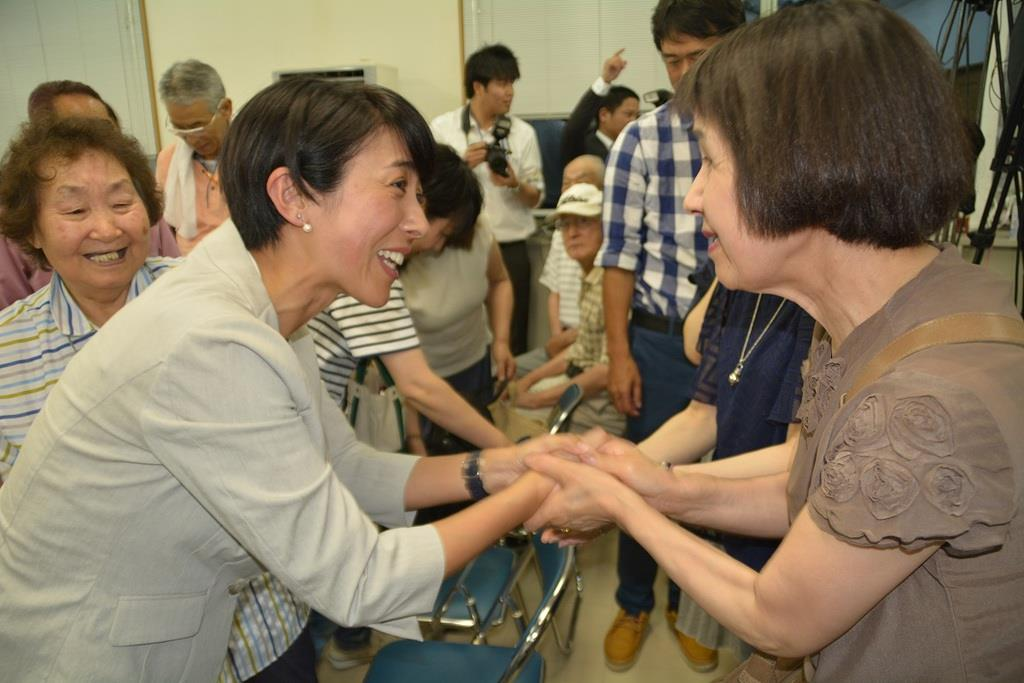 接戦の末に初当選を決め、支持者らから握手ぜめにされる寺田静氏=21日、秋田市