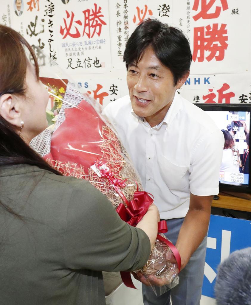 大分選挙区で当選を決め、支持者から花束を受け取る安達澄氏=21日深夜、大分市