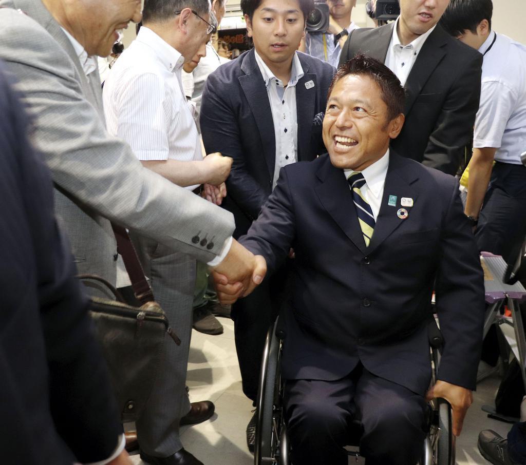 岩手選挙区で当選を決め、支援者と笑顔で握手する横沢高徳氏=21日深夜、盛岡市