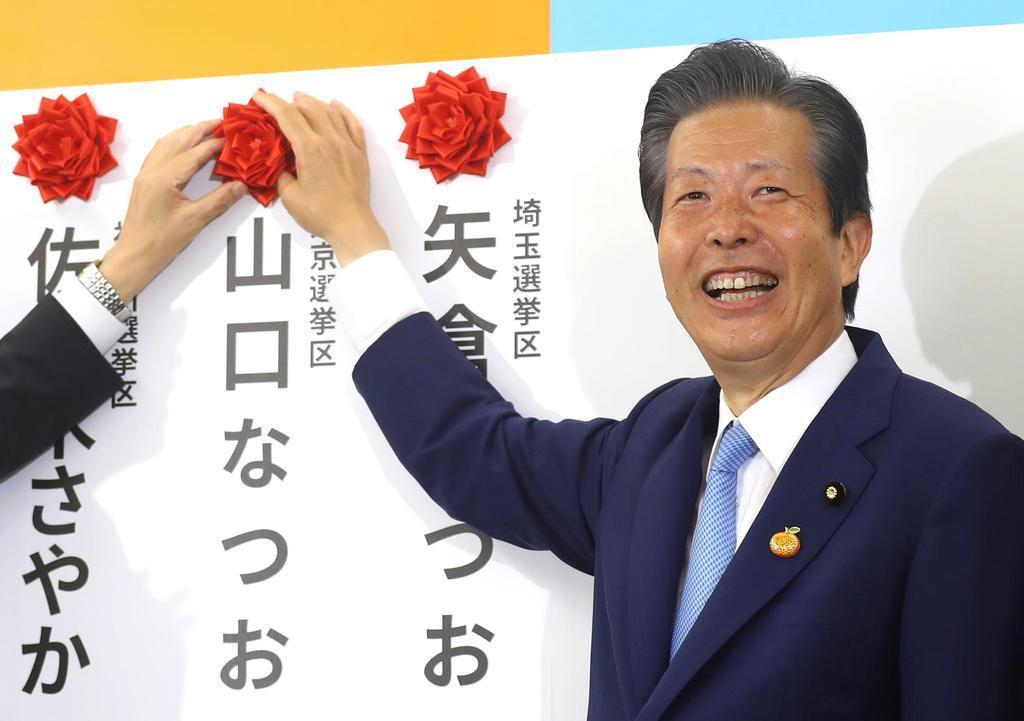 みずからの当選を示す花を笑顔でつける公明党の山口那津男代表=21日夜、公明党本部(桐山弘太撮影)