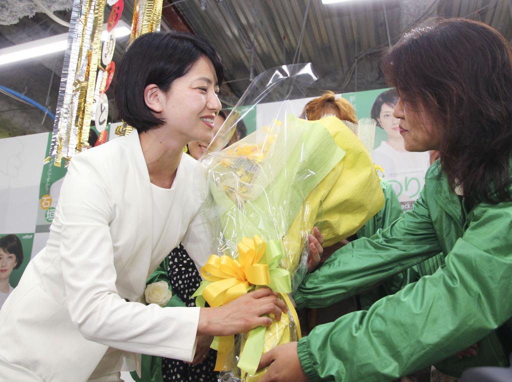 宮城選挙区で当選を決め、支援者から花束を受け取る立憲民主党の石垣のり子氏(左)=22日未明、仙台市