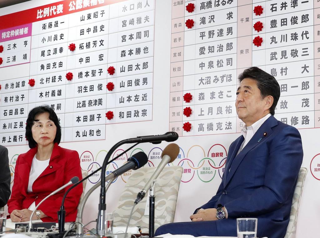 自民党本部の開票センターで、テレビ局のインタビューに答える安倍首相(右)=21日午後10時41分、東京・永田町