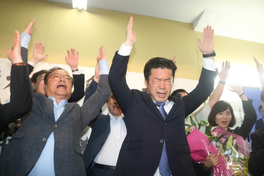 当選が決まりバンザイする自民党新人の加田氏=神戸市中央区