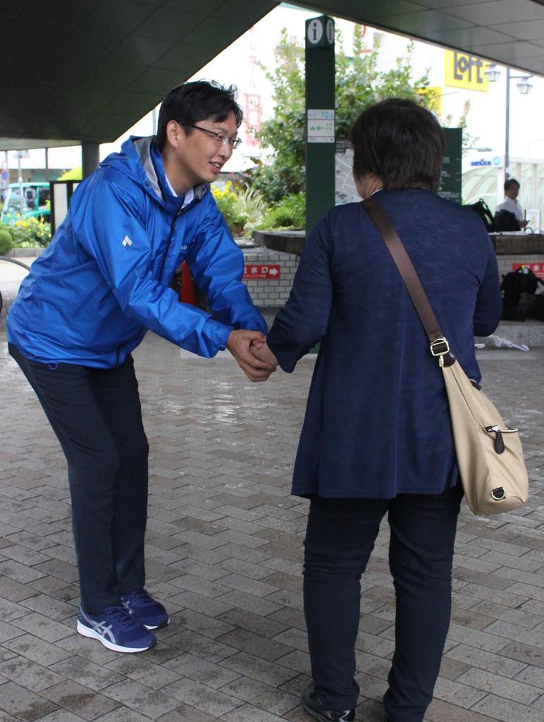 初当選を祝福され、握手をする兵庫選挙区の公明新人、高橋光男氏=22日午前、神戸市中央区