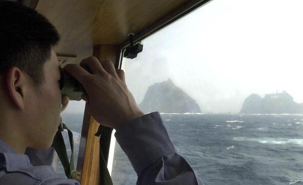 竹島の様子を見る韓国海洋警察庁の職員=23日(AP)