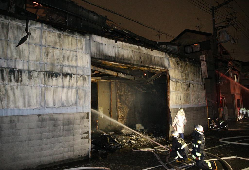 火災のあった工場で消火活動をする消防隊員ら=23日午後、大阪府守口市(寺口純平撮影)