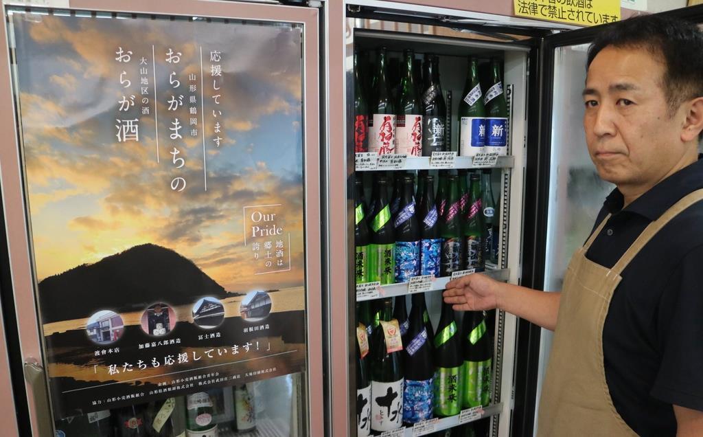 作成した支援ポスターを前に「大山地区の蔵元に支援を」と呼びかける山形小売酒販組合青年会の浅野隆志会長=山形市小立(柏崎幸三撮影)