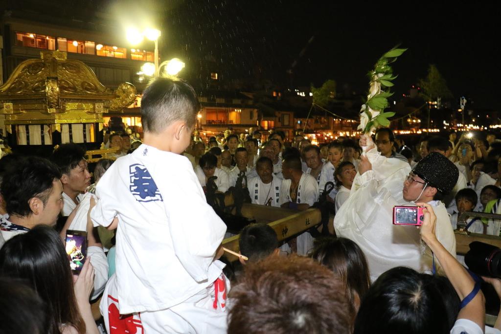 神職が榊で神輿に水をかけると大きな歓声があがった=京都市下京区