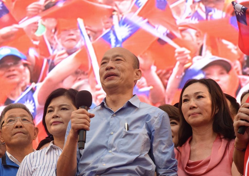 台北市の集会で登壇した国民党の韓国瑜氏。背景のスクリーンに映し出された会場は、台湾の旗で埋め尽くされている。韓氏の右は妻の李佳芬氏=6月1日(田中靖人撮影)