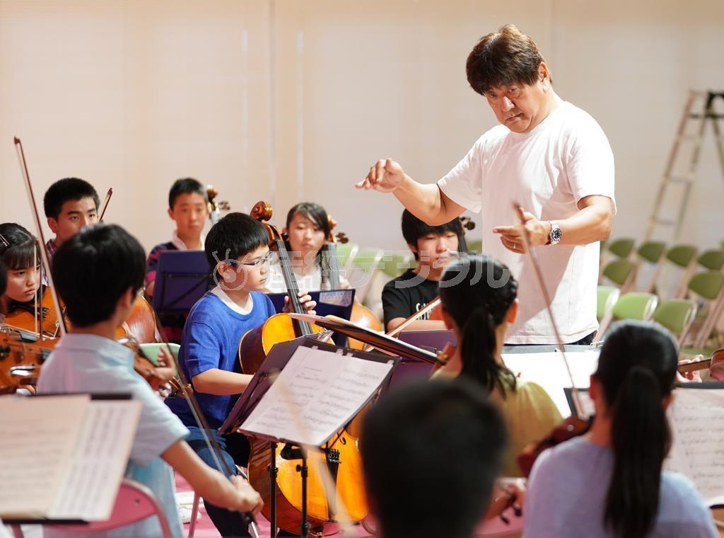 「スーパーキッズ・オーケストラ」の演奏を指導する佐渡裕さん。「聞く人の心に届くように」と語りかける =神戸市長田区(恵守乾撮影)