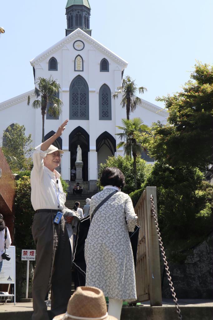 大浦天主堂を案内する「長崎巡礼センター」事務局長の入口仁志(左)