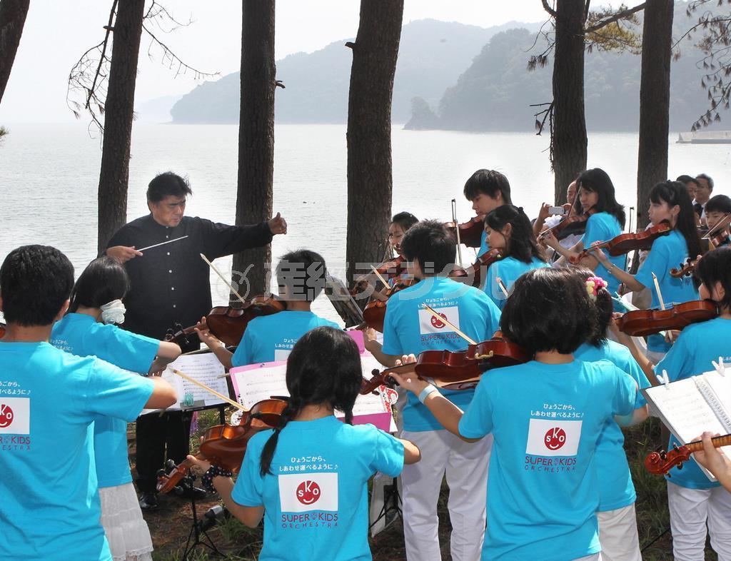 東日本大震災の津波による犠牲者が眠る海に向かい鎮魂の演奏をする佐渡裕さんとスーパーキッズ・オーケストラ =平成23(2011)年8月、岩手県釜石市根浜海岸
