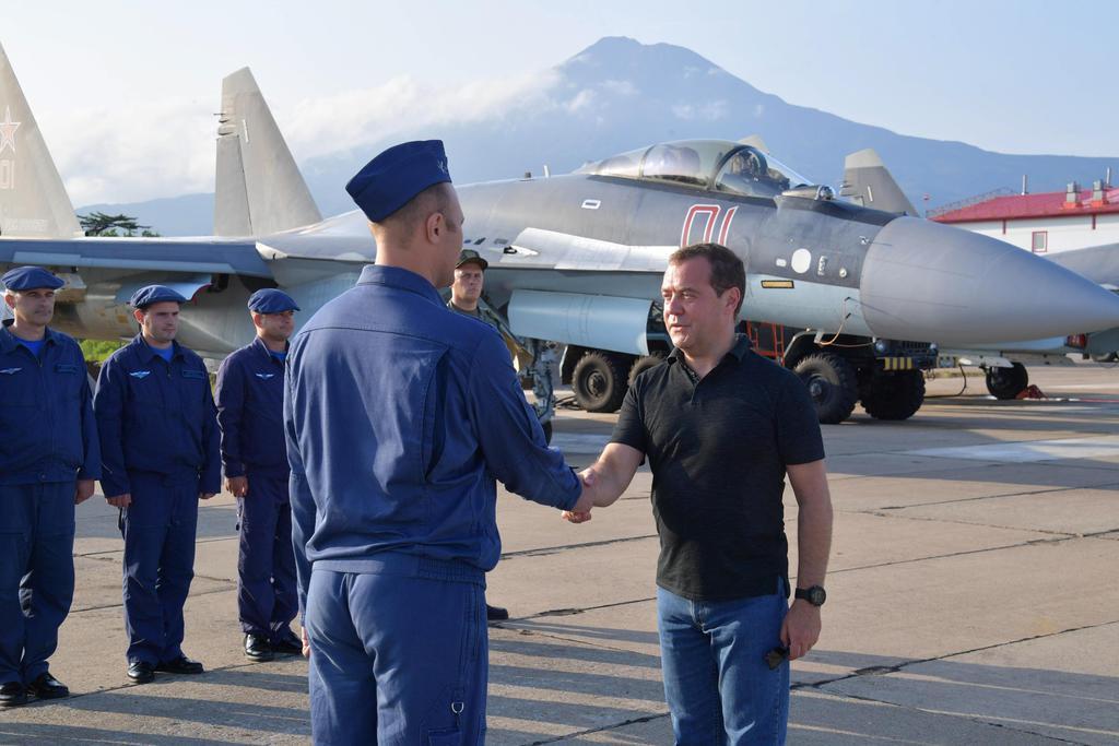 2日、択捉島でロシアのスホイ35戦闘機の乗員と対面するメドベージェフ首相(右端)(タス=共同)