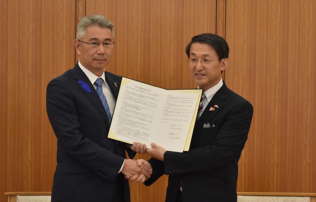 災害時の物資輸送に関する協定を結び、握手を交わす鳥取県水難救済会の西村博文会長(左)と平井伸治知事=鳥取市
