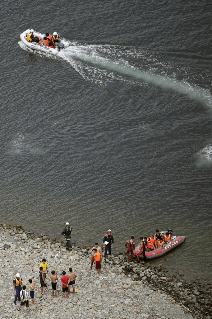 神戸大のボートが転覆し、現場近くの海岸に集まる人たち=6日午前11時30分、兵庫県洲本市