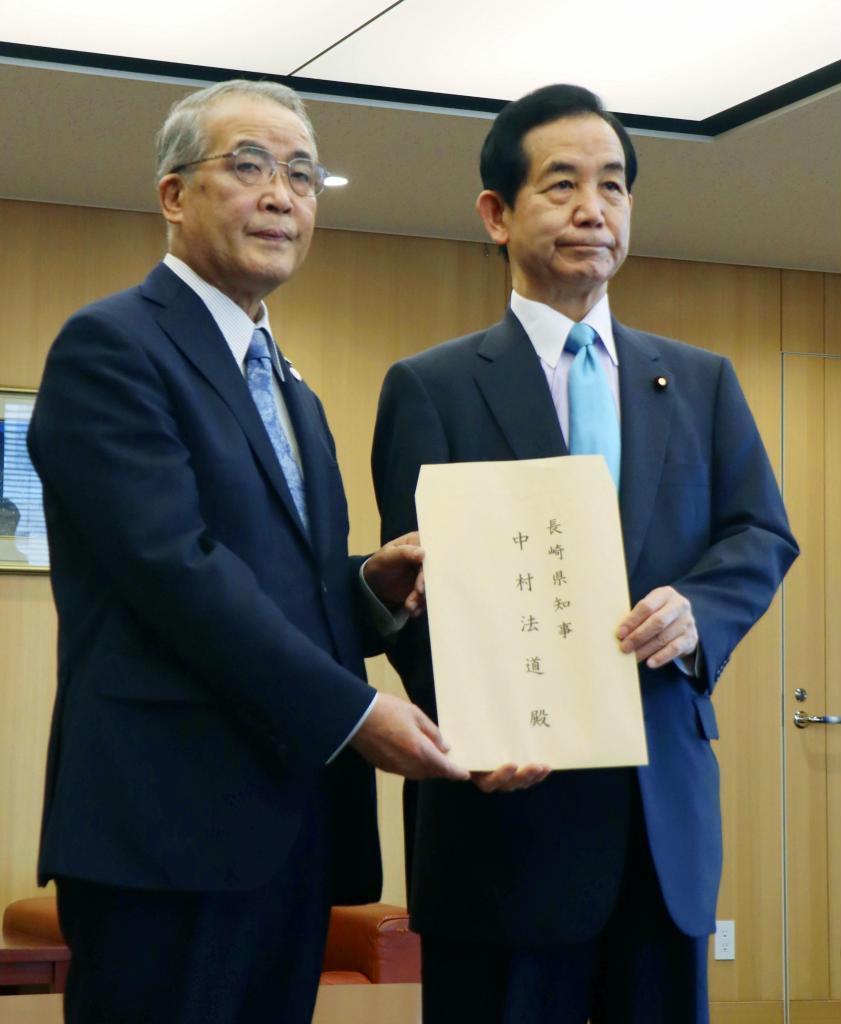 与党検討委員会の山本幸三委員長(右)から文書を受け取る長崎県の中村法道知事