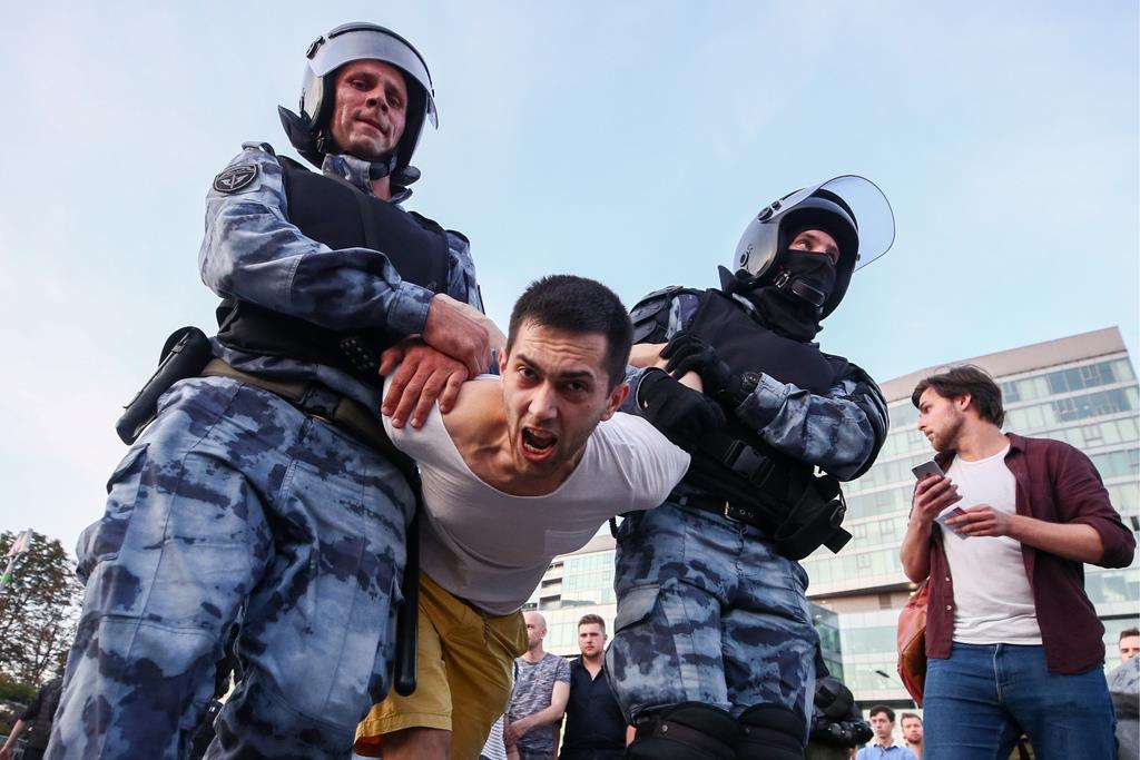 27日、モスクワで市選管の不正疑惑に抗議し特殊部隊に拘束される男性(タス=共同)