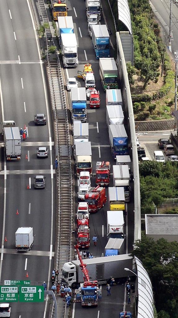 名神高速道路下り線の事故現場で、横向きに車線をふさいだ大型トラック=8日午前、大阪府吹田市(本社ヘリから、前川純一郎撮影)