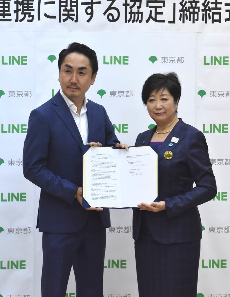 特殊詐欺防止に向けて連携協定を締結したLINEの出沢剛社長(左)と小池百合子知事=9日午後、都庁