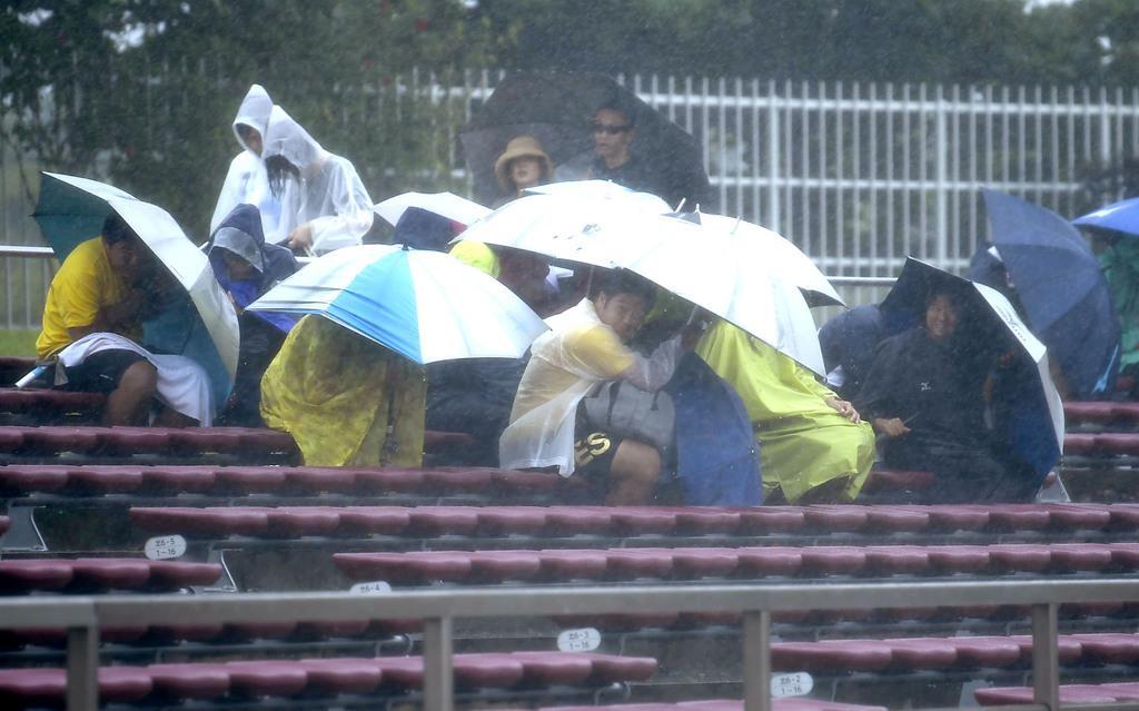 台風9号の影響で全国高校総体の陸上競技が中断し、スタンドで強風と大雨をしのぐ人たち=8日午前11時22分、沖縄県沖縄市