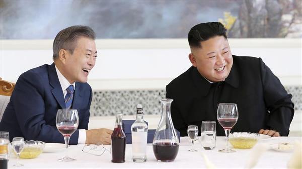 平壌の老舗冷麺店「玉流館」での昼食会で韓国の文在寅大統領(左)から贈り物を受け取り笑顔の北朝鮮の金正恩朝鮮労働党委員長=9月19日(平壌写真共同取材団)