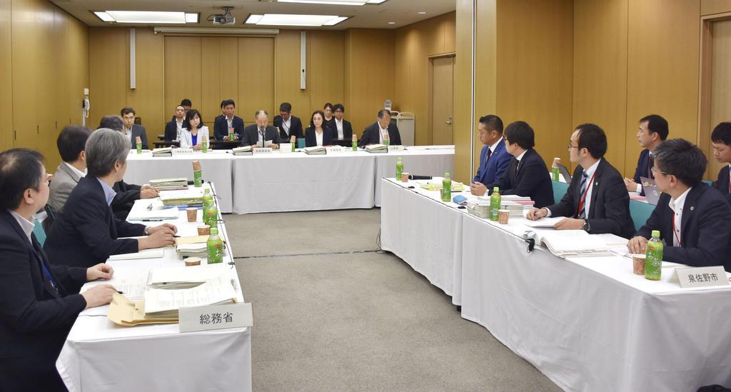 ふるさと納税を巡る国地方係争処理委員会の会合で、総務省の担当者ら(左側)と対峙する大阪府泉佐野市の代表者(右側)=7月、総務省