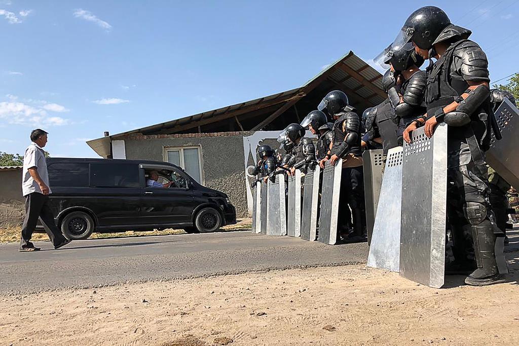 8日、キルギス首都ビシケク郊外にあるアタムバエフ前大統領の自宅周辺で拘束作戦に当たる治安当局者ら(タス=共同)