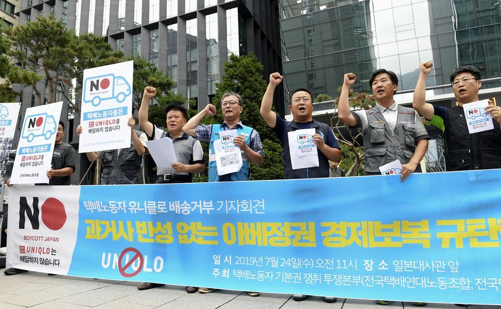 ソウルの日本大使館前で記者会見する配達員らの労働団体のメンバー(共同)