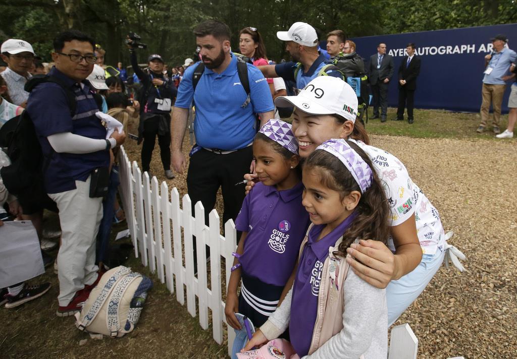 全英女子オープン勝利後、子供たちとの撮影に笑顔で応じる渋野(手前から2人目)=4日、ミルトン・キーンズ近郊(AP)